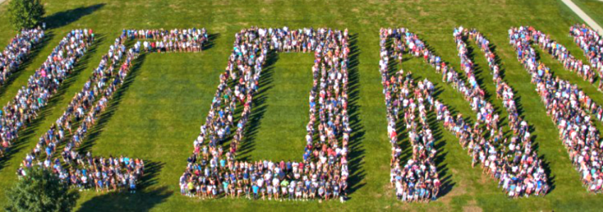 an aerial view of UConn students standing on the Great Lawn in a formation that spells UConn