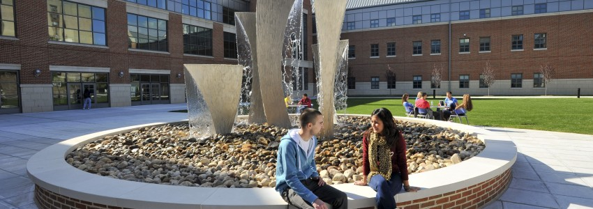 students sitting next to a fountain at the Waterbury campus